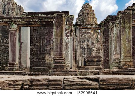 Prasat Bayon with smiling stone faces is the central temple of Angkor Thom Complex, Siem Reap, Cambodia. Ancient Khmer temple with frescoes and columns, World Heritage. Selective focus
