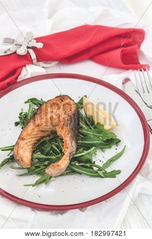 Baked Steak Trout Fish On Green Leaves Of Rucola Lettuce, Lemon, Served On White Plate Serving, Top