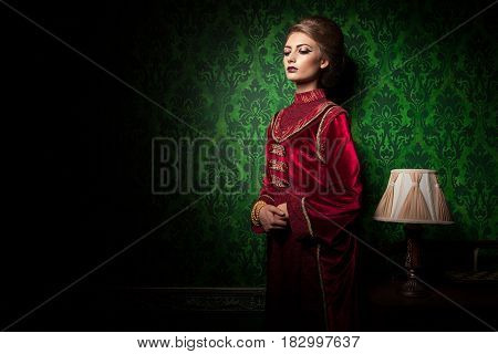 Rich woman dressed vintage clothes in retro interior. Rococo period. Luxury and high class