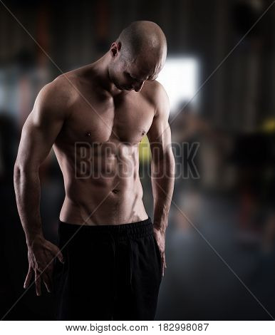 Muscular man with perfect fit on gym background