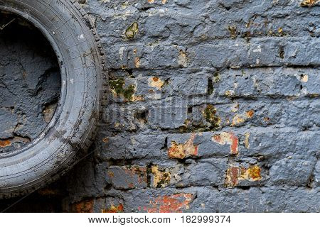painted in grey tyre lies on the gray brick wall