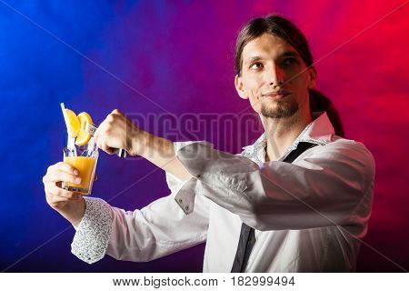 Alcohol liquor party drinking concept. Barman mixing beverages in glass. Male tapster holding drink glass.