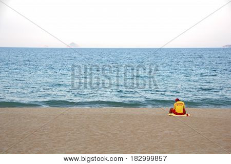 There is nobody to save. Lonely lifeguard sitting on empty beach. Nha Trang, Vietnam.