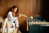 Beautiful woman in sauna pouring oils on hot stones to clean airways poster