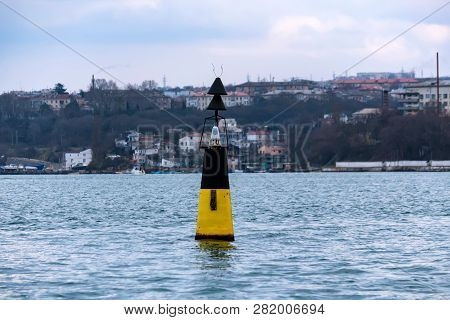 Close View Of Black And Yellow Beacon In Black Sea
