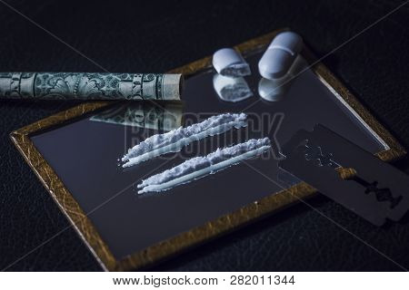 Conceptual Image Of Drug Abuse With Two Lines On A Mirror And A Half Chopped Pill