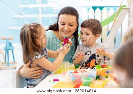 Teacher With Kids Working With Plasticine At Kindergarten Or Playschool