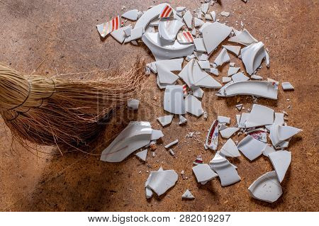 Straw Broom Sweeping Pieces Of Shattered Dishes. Splinters And Fragments Of The Broken White Ware On