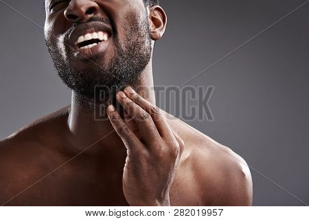 Close Up Of A Dissatisfied Afro American Man Taking Care Of His Beard