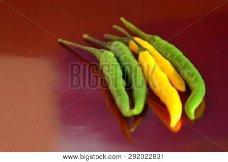 Fresh Yellow And Green Hot Chilli Peppers On Red Background, Studio Shot