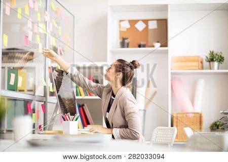 Young Businesswoman Sitting By Workplace And Stretching Arm To Take Notepaper From Noticeboard Durin
