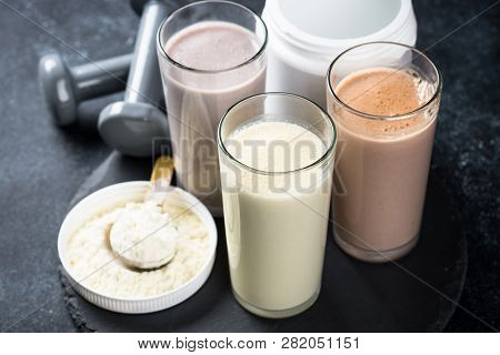 Fitness Concept, Sports Nutrition. Protein Cocktails, Protein Powder And Dumbbell. Vanilla, Berry An