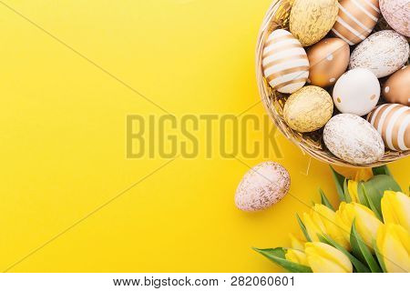 Flat Lay Of Golden Easter Eggs In Nest With Tulips On Yellow Background. Easter Background Or Easter