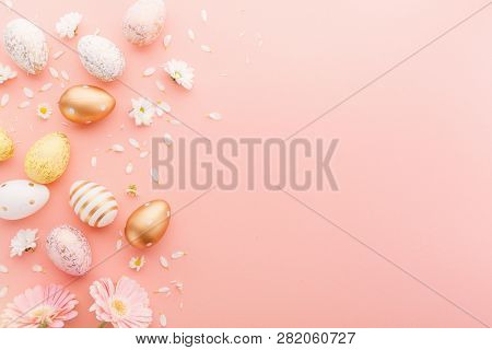 Flat Lay Of Golden Easter Eggs With Small Flowers And Petals On Pink Background. Easter Background O