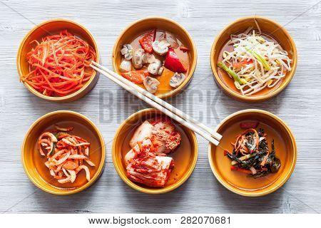Korean Cuisine - Chopsticks Above Various Appetizers (banchan Or Panchan) In Ceramic Bowls On Gray T