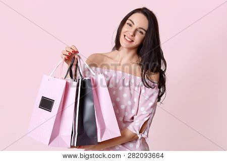 People And Shopping Concept. Happy Dark Haired Woman Shopaholic Dressed In Polka Dot Dress, Carries