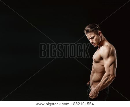 Muscular Model Young Man On Dark Background. Fashion Portrait Of Strong Brutal Guy With Trendy Hairs
