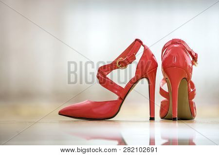 Pair Of Fashionable High Heel Leather Red Cut-out Female Shoes With Golden Buckles Isolated On Light