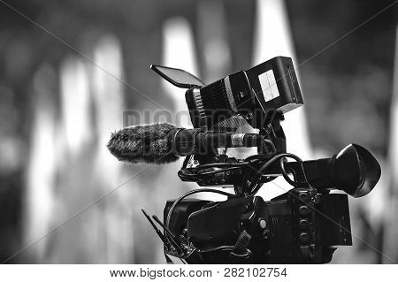 Modern Digital Television Or Video Camera, Camcorder, Recorder In Studio On Blurred Colorful Backgro