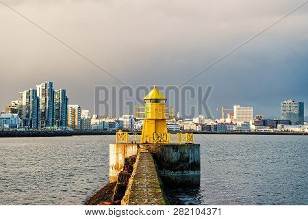 Lighthouse In Reykjavik, Iceland. Lighthouse Tower And Stone Pier In Sea. Seascape And Skyline On Gr