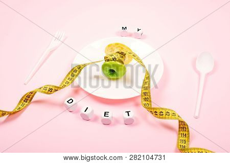 Apple Core With Measuring Tape In Place Of The Waist On A White Plate With Text My Diet On Pink Back