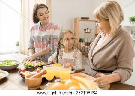 Kind grandma cuddling her granddaughter while cooking breakfast by table in the kitchen