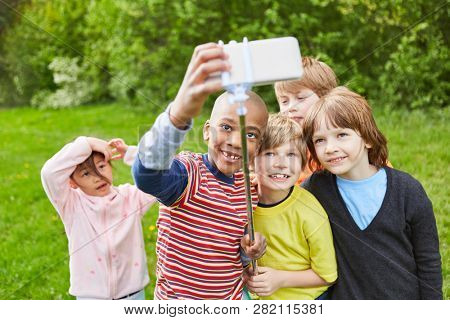 Laughing group of kids together is taking a selfie with smartphone on selfie stick
