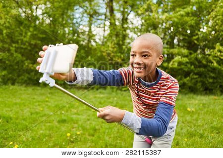 African boy in the park is taking a selfie with the smartphone on the selfie stick
