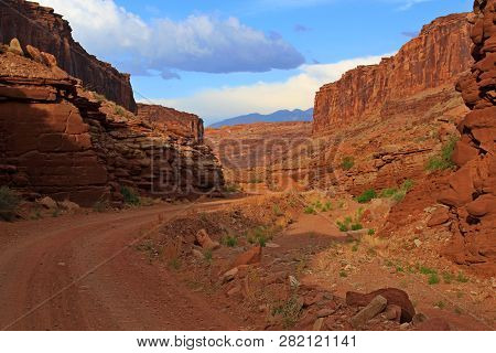 Clear blue skys with puffy white clouds lead you out from a deep canyon jeep trail poster