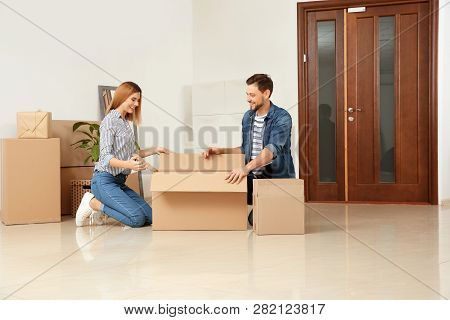 Happy Couple Unpacking Moving Box In Their New House