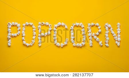 The Word Popkorn Is Laid Out From Pieces Of Salt Popcorn On A Yellow Background. Top View. Flat Lay