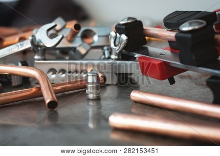 Pipes, Pipe Bender And Other Pipework Tools On A Fitter Workbench Background.