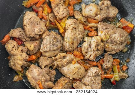 Top View On A Pan With Turkey Meat Pieces Fried In Sunflower-seed Oil And Vegetables