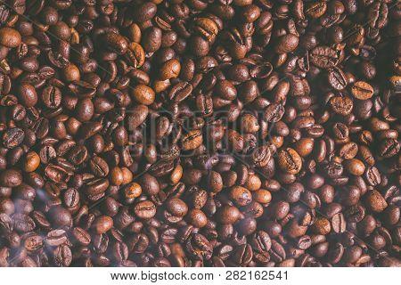 Fresh Brown Coffee Beans Smokey Vintage Background.
