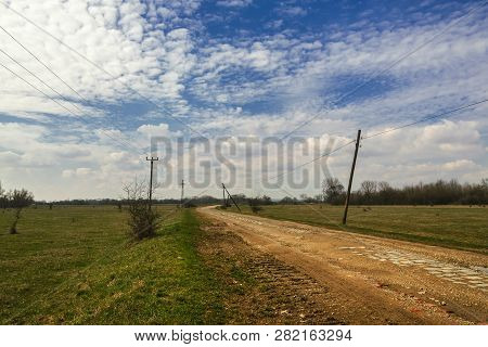 Countryside Landscape In Springtime. Sunny Day In Rural Landscape. Country Road Through Fields. Coun