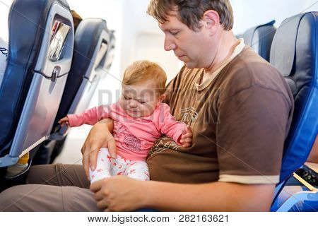 Young Sad Tired Father And His Crying Baby Daughter During Flight On Airplane Going On Vacations. Da