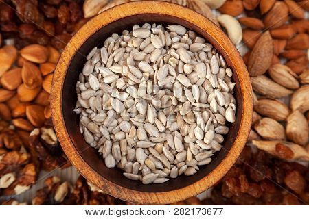 Sunflower Seeds In A Wooden Cedar Plate On The Background A Scattering Of Various Nuts. Peeled  Sunf