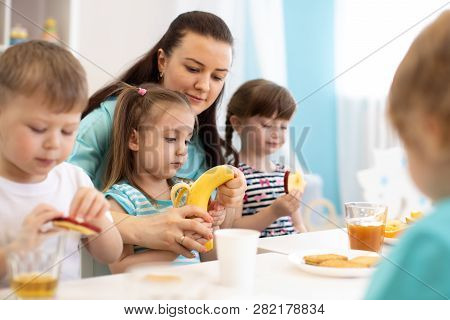Kids Have Lunch. Children And Carer Together Eat Fruits In Kindergarten Or Day Care Center