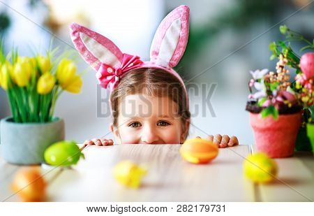 Happy Easter! Funny Child Girl With Rabbit Ears And  Eggs At Home In Kitchen