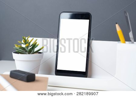 Modern Office Stationery On White Table And Dark Grey Wall. Mobile ,pencil, Notepad,ruler,pen And Pe