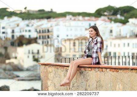 Full Body Portrait Of A Happy Teenager Contemplating Landscape On A Ledge