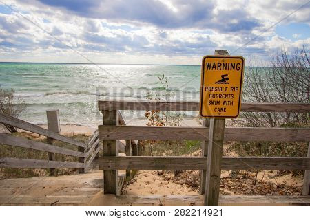 Rip Current Warning. Sign At Beach Entrance Warning Of Dangerous Rip Currents As Waves Crash On To T