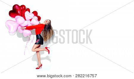 Valentine Beauty girl with colorful air balloons laughing, isolated on background. Beautiful Happy Young woman. holiday party. Joyful model having fun, dancing and celebrating with red color balloon