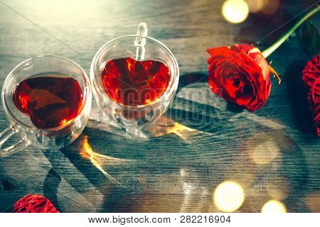 Valentine heart shaped tea cup with red hearts rattan decor and roses on wooden background. St. Valentine's Day, Love concept. Top view, tabletop. Cafe, dating. Valentine's Day romantic dinner, party