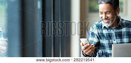 Banner Of Happy Mature Asian Or Hispanic Old Man Looking At Smartphone Smiling Positive In Casual Li