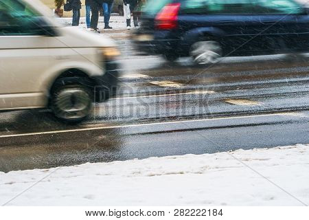 Crosswalk. Slippery Wet Asphalt City Road In Winter. Driving Cars Are Blurred In Motion. Waiting For
