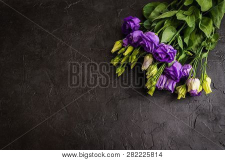 Beautiful Bouquet From Purple Eustoma Flowers On Black Texture Background. Copy Space, Top View
