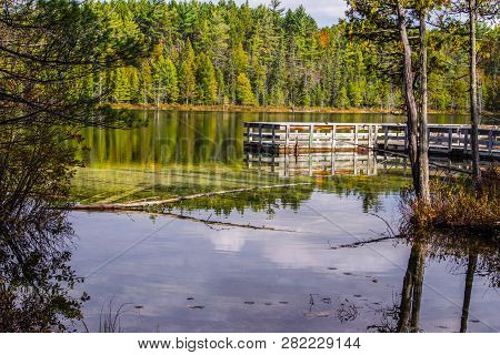 Wilderness Fishing Dock On Lake. Wilderness Lake Surrounded By A Lush Northern Forest With A Fishing