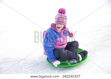 Belarus, The City Of Gomel, January 07, 2018.central Park.sledding Off A Snow Slide.a Girl In A Wint