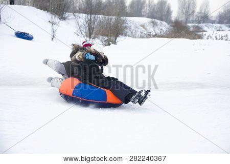 Belarus, The City Of Gomel, January 07, 2018.child Sledding Cheesecake.sledding Off A Snow Slide.kid
